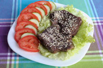 Veal on a piece of lettuce with tomatoes and cucumbers