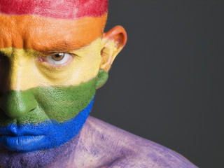 Gay flag painted on the face of a man, serious expression.