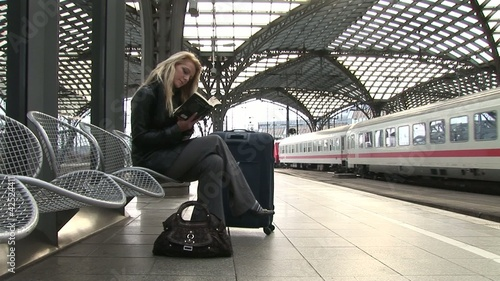 Business woman waiting and reading a book on central station