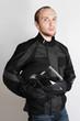 young motorcyclist man holding helmet in studio