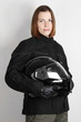 young motorcyclist woman holding helmet in studio