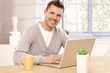 Handsome man browsing internet at home smiling