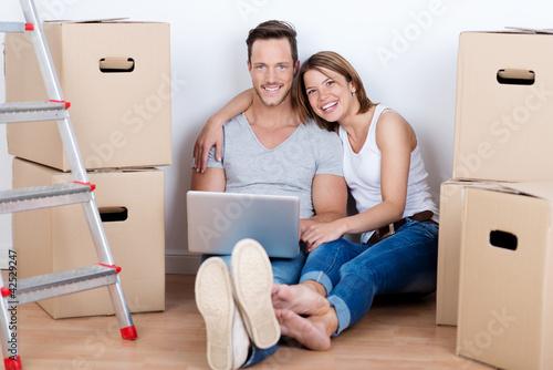 lachendes paar mit laptop zwischen kartons