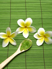 frangipani and Green salt in wooden spoon a on green mat