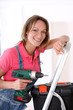 Woman standing on scale with electric drill