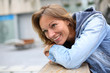 Smiling adult woman with blue jeans jacket in town