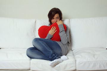 Ragazza con cuore su divano