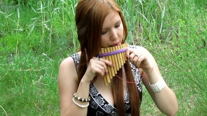 redhead girl flute player outdoors in spring meadow