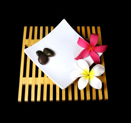 Tropical plumeria flowers on a wooden grid