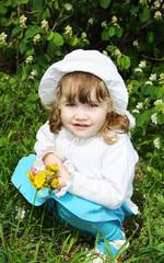 Beautiful little girl holds yellow dandelions