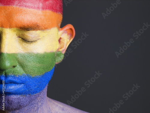 Gay flag painted on the face of a man with closed eyes.