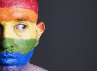 Gay flag painted on the face of a man. Man is looking sideways