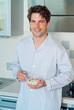 Junger Mann steht in Küche und frühstückt