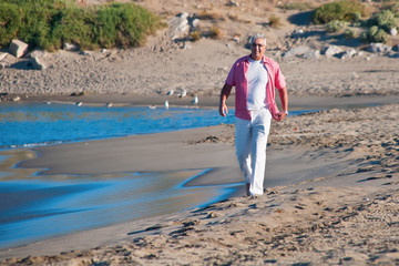 Happy mature man walking on the beach