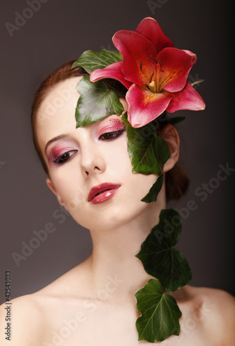 Portrait of red-haired girl with flower and make-up.