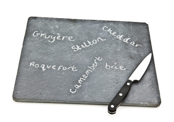 Slate cheese board with cheede names and knife on white backgrou