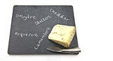 Stilton cheese on slate cheeseboard with knifewith wite backgrou