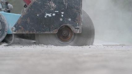 Concrete saw cutting through sidewalk
