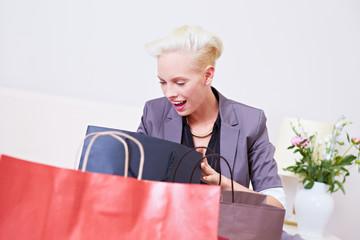 Staunende Frau schaut in Einkaufstüte