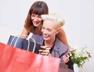 Lachende Frauen schauen in Papiertüten