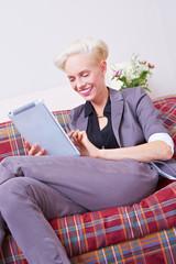 Lachende Frau liest Ebook auf Sofa
