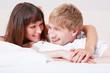 Junges Paar im Bett lacht sich an