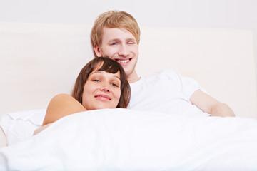 Paar liegt gemütlich im Bett