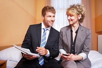 Geschäftsmann neben Businessfrau zeigt auf Zeitung