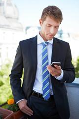 Geschäftsmann schaut auf Smartphone