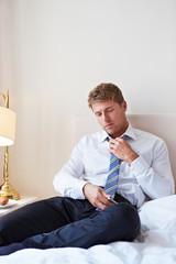 Erschöpfter Geschäftsmann lockert Krawattenknoten