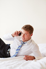 Geschäftsmann im Bett telefoniert