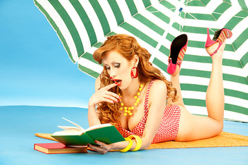 Beautiful sexy girl pin up on beach under sun umbrella