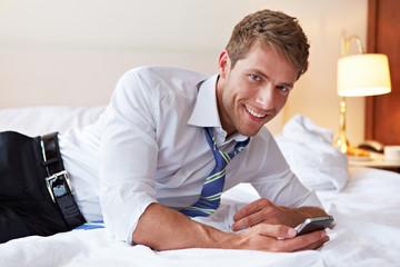 Manager mit Smartphone im Bett