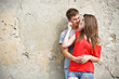 Young couple is standing grunge wall