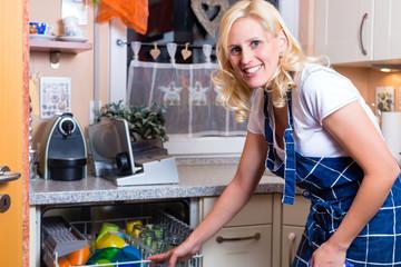Hausfrau beim Geschirr abwaschen mit Geschirrspüler