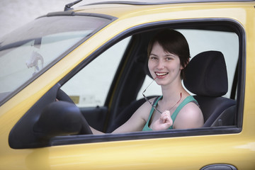 Happy woman in her car with glasses