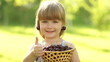 Happy child with a basket of fruit cherries. Thumbs up. Ok