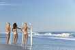 Three Beautiful Women Surfers In Bikinis Surfboards At the Beach