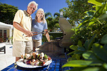 Happy Senior Couple Outside Cooking on A Summer Barbecue