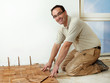 Smiling carpenter at work is fitting wood parquet on the floor