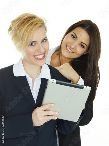 Two beautiful girls having fun with tabletpc
