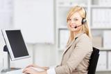 blonde frau mit headset und computer im büro