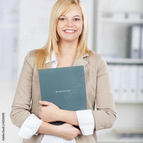 lächelnde bewerberin mit ihrer mappe