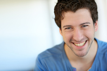 Portrait of cheerful young guy with blue eyes