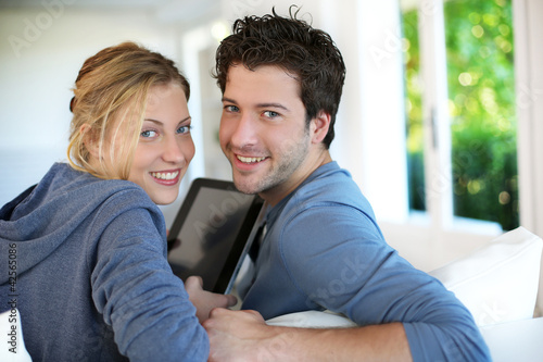 Young couple using electronic tablet