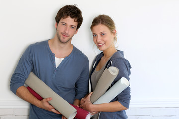 Portrait of young couple holding wallpaper rolls