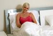 Frau sitzt im Bett und lacht