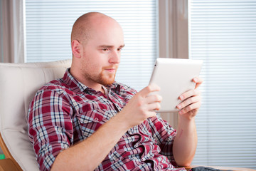 Focused man working and playing with tablet computer (lots of co