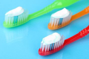 Toothbrushes with paste on blue background