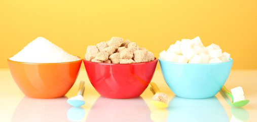 Colorful bowls with different types of sugar with colorful